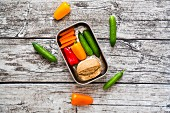 Spelt roll with cream cheese and carrots, peppers and cucumbers in a metal box