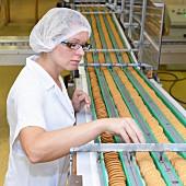 Frau kontrolliert Kekse auf dem Förderband in einer Backfabrik