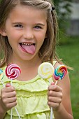 A little girl holding three lollipops