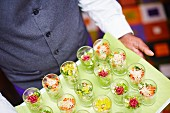 A waiter carrying a tray of individual salads in glasses