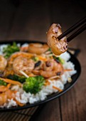 Prawn stir fry with rice, broccoli and carrots; in the foreground a glazed prawn between two chopsticks