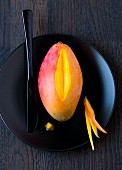 A mango on a black plate (partially sliced)