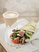 A salad and bacon wrap served with coffee