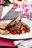 A grilled beef steak on a pepper medley served with bread