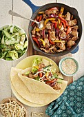 Teriyaki pork in a pan and wrap served with salad