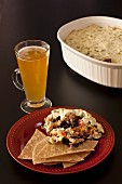 Baked layered dip with tortilla chips and beer (Mexico)
