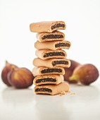 A stack of fig rolls with fresh figs in the background