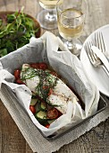 Baked fish with courgette and tomatoes and parchment paper
