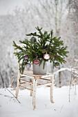 Fichtenzweige mit Christbaumkugeln dekoriert auf einem Shabby-Stuhl im Schnee