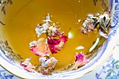 Floral tea with dried flowers floating in it