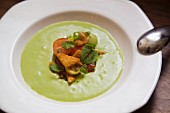 Cream of pea soup with croutons and tomatoes