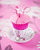 A pink flower cupcake in an espresso cup