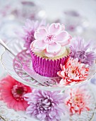 A cupcake decorated with a fondant flower