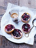 Berry tartlets with icing sugar served with coffee