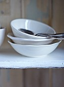 Soup bowls, bowls and spoons on a kitchen shelf