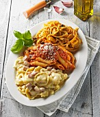 Three pasta dishes on an oval platter garnished with basil