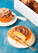 A cupcake filled with orange jelly and topped with chocolate ganache