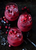 Three whiskey and cranberry cocktails with ice cubes