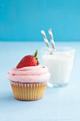 A strawberry cupcake served with a glass of milk