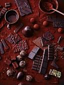 Verschiedene Schokoladensorten und Pralinen auf Kakaopulver