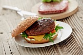 A cheeseburger with tomatoes and rocket