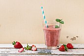 A glass of strawberry smoothie with chia seeds, fresh strawberries and mint