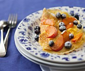 Sweet omelette with blueberries, peaches and icing sugar