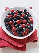 Various fresh berries in a bowl on a tea towel