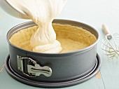 Cheese mixture for a cheesecake being poured into a baking tin lined with pastry