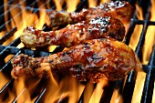 Three chicken legs in BBQ sauce cooking on a flaming grill