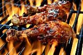 Drei Hähnchenschenkel in BBQ-Sauce auf dem flammenden Grill