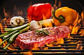 Beef steak with rosemary, red and yellow peppers, fresh garlic and spring onions on a flaming barbecue
