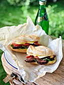 A grilled steak sandwich with mustard, cheese, tomatoes and spinach in parchment paper on a picnic basket