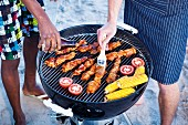 Kebabs, tomatoes and corn cobs on a grill