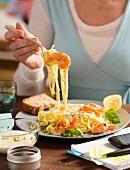 Frau isst Bandnudeln mit würzigen Garnelen zum Lunch
