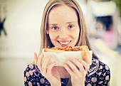 A young woman with a pulled pork sandwich
