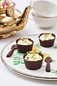 Pistachio mousse in chocolate bowls with chocolate spoons
