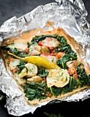 Ein Stück Pizza mit Spinat, Artischocken und gefüllten Oliven
