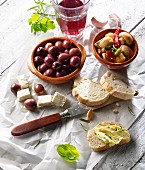 Appetisers of olives, mushroom salad, goat's cheese, bread and red wine