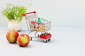 A mini shopping trolley filled with toy foodstuffs next to apples and a bulb of fennel