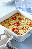 Oven-baked frittata with tomatoes, cheese, spring onions and herbs