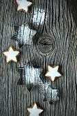 Ausstechförmchen-Sterne mit Puderzucker und Zimtsterne auf Holzbrett