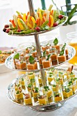 Appetisers in square glasses on a large silver cake stand