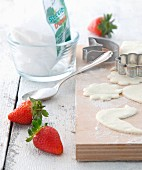 An arrangement of strawberries, Stevia powder and unbaked biscuits