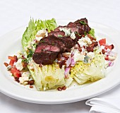 Hanger steak on lettuce hearts with bacon and blue cheese