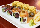 Various types of sushi with wasabi and ginger on a serving platter