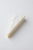A slice of Brie de Meaux on a white surface