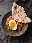 Vegetarian egg curry with garam masala and tomatoes served with chapatisis