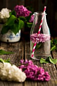 Lilac flower water in a bottle with a straw
