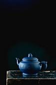 A blue ceramic teapot against a black background